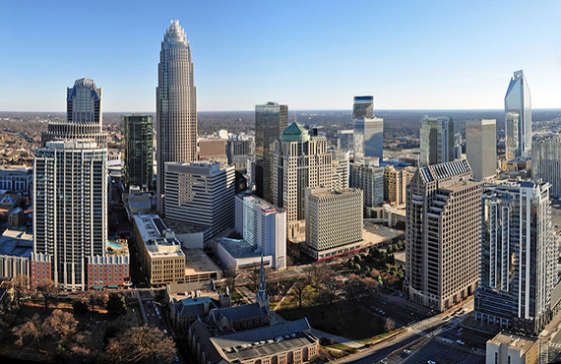 The skyline of the city of Charlotte, NC. Features high rises and other tall buildings, both residential and office. Some trees can be seen below. A bright and sunny day - things to do in Charlotte, NC