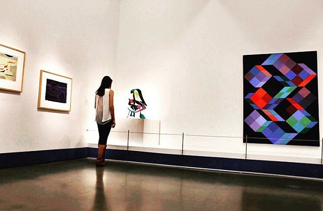 A large painting hangs on a white wall, to its left a woman (me) stands looking at a small modern sculpture. To her left, two smaller paintings appear. The room is otherwise empty. Things to do in Charlotte NC - Visit the Bechtler Museum.