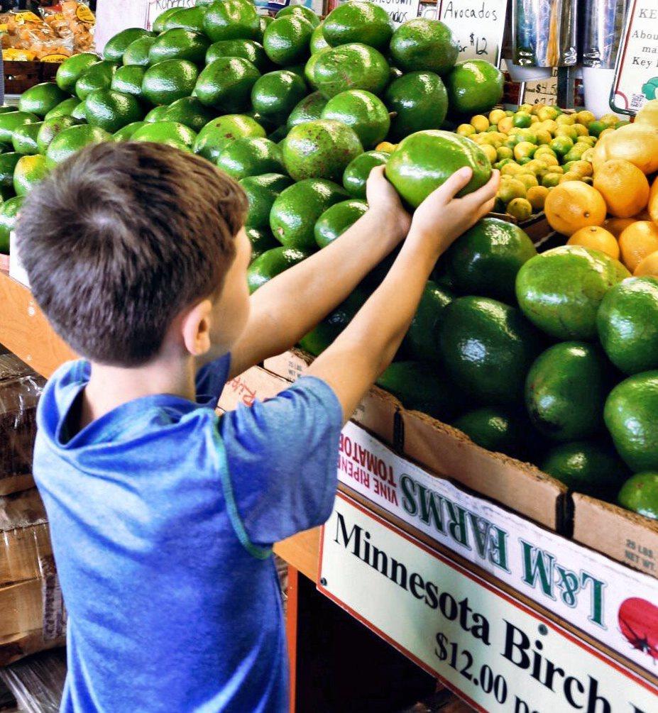 boy holding green citrus fruit