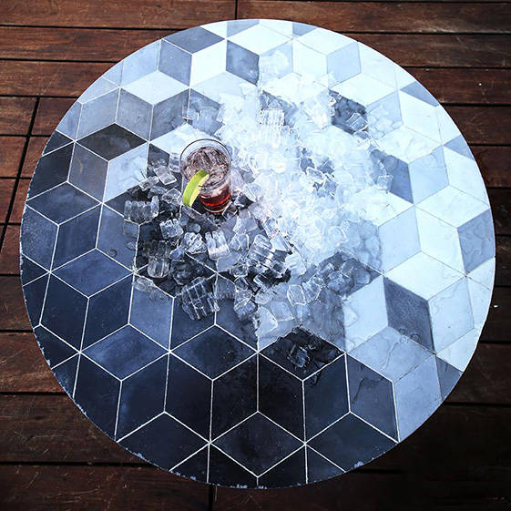 a large black and white coffee table with ice spilled all over and a drink