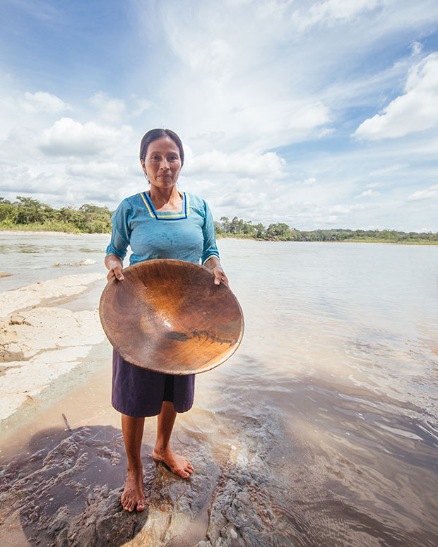 A native amazonian woman holding a bowl on a beach.