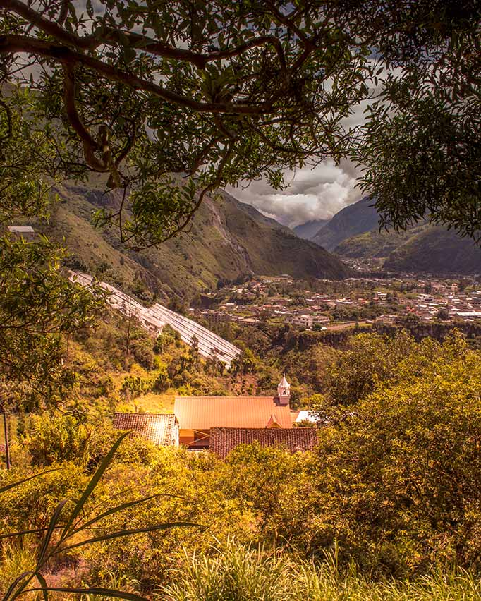 A view of a small church, sky and trees in Banos - ecuador vacation hike