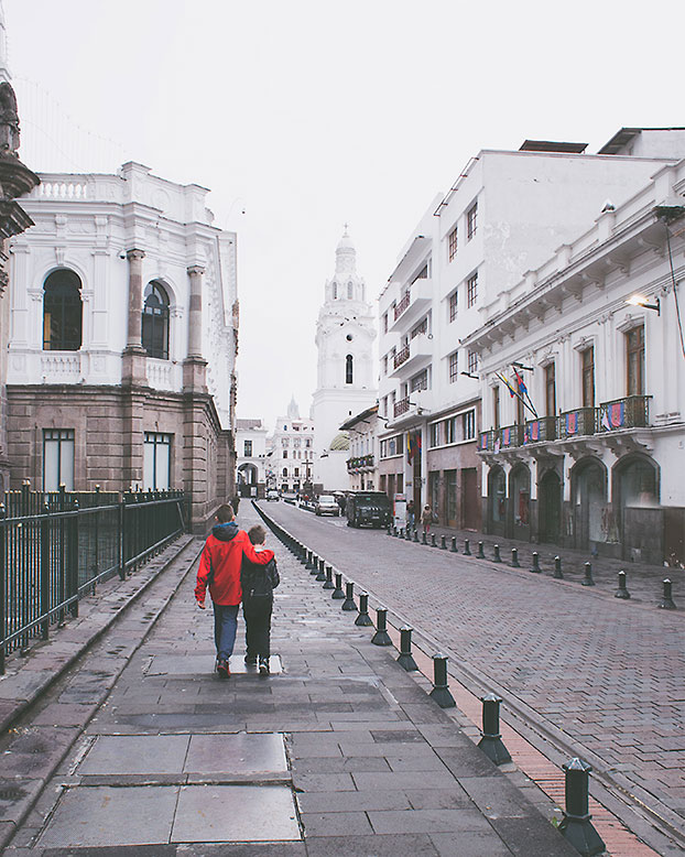 two children walking down a quito street in early morning