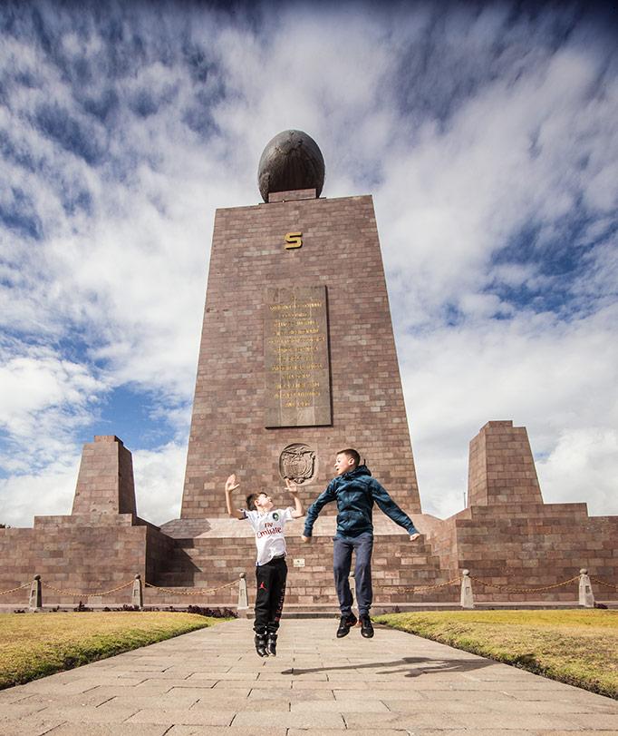 Two boys jumping in center of the world, quito, ecuador.