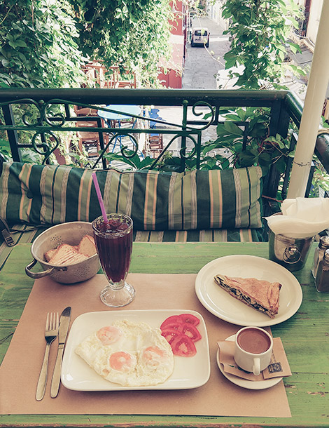 A traditional Greek breakfast consists of coffee, bread, eggs, juice and pie.  A picture of a comofortable seat surrounded by leaves and a street in the background.