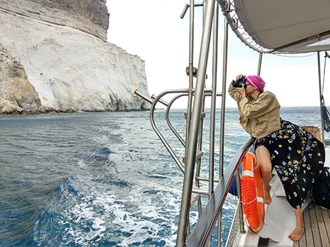 A woman (me) wearing a long dress and a bandana on her head, leans out of the side of the boat, camera in hand.  In the background soft Kleftikos rock and water.