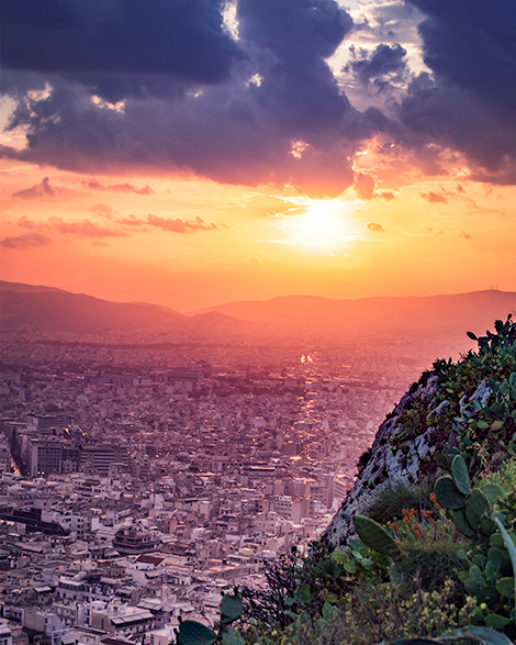 A view from mt. Lycabettus in Athens. Buildings in the foreground and the sunset in the background. In the extreme foreground some plants included cactus. Greece off the beaten path a seven day itinerary