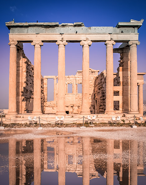 A ruined building with neoclassical columns inside the Acropolis, an ancient green structure.  The structure is reflected in the puddle on the ground.