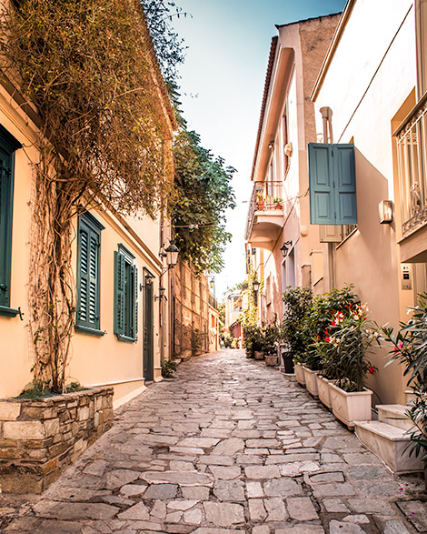 An attractive cobblestone street lined with well cared town homes that appear to have been build before the 20th century.  Plants line the streets.   Things to do in athens - plaka