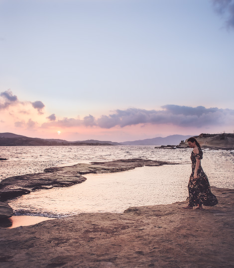 A woman (me) stands on a rocky shore.  Sun slowly rises over the horizon and water can be seen in the foreground.