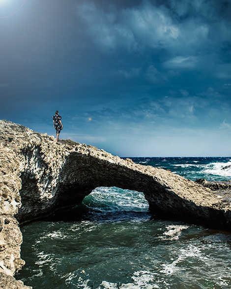 A woman (me) stands on a large rock that hangs out over the ocean.  Large waves hit the rock at the bottom.  Photograph taken in Milos, Greece.     Things to do in Milos