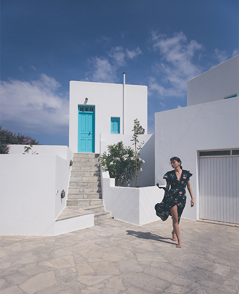 A woman (me) walks next to a typical Greek home with white walls and blue door.  The sky is clear and it is a sunny day.