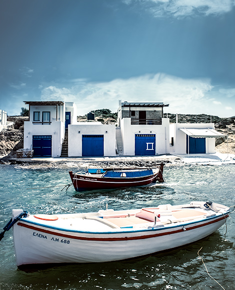 In the background, four narrow Greek style homes are build into the rock.  Each home has a large door at the bottom, big enough for a boat to pass.  In the foreground, two small fishing boats rest in calm bay waters.  A typical scene in Ag. Konstantinos, Milos, Greece.