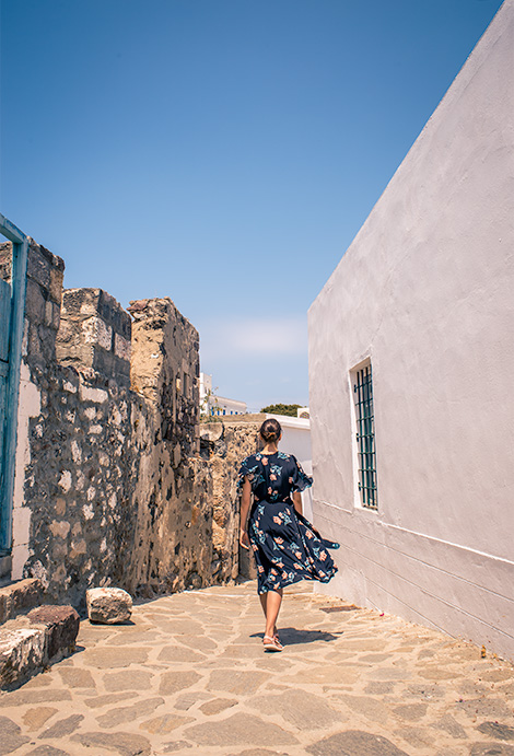 A woman (me) walking away from the camera on a narrow, cobblestone, traditional greek street.