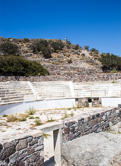 A typical Roman amphitheater.  A large semicircle constructed of ancient stones with seating.  Well preserved, rocks are mostly in place and only a little grass grows on the floor.  The Milos Roman theater