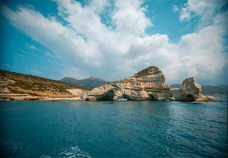 Soft rock and cliffs as seen in Kleftikos Bay. A sunny day with blue skies overhead and blue water beneath.