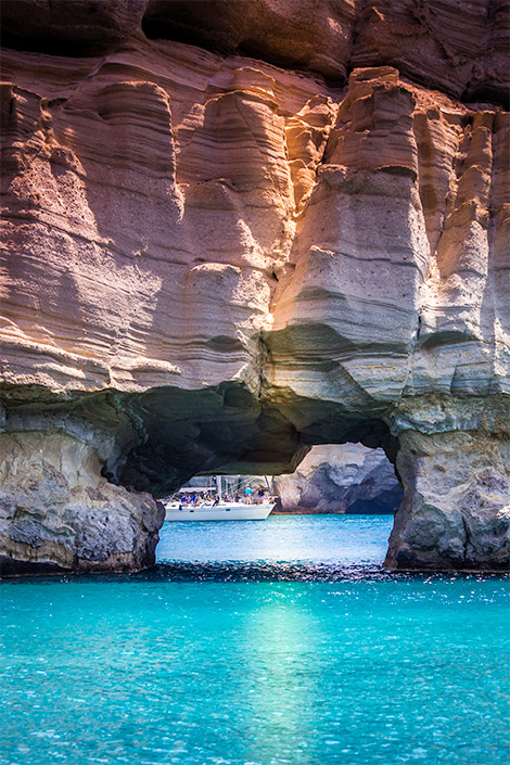 A large soft rock in Kleftikos bay takes up most of the photograph.  Through the opening in the rock, a boat with passengers.  The rock is resting in blue water. Things to do in Milos, Greece