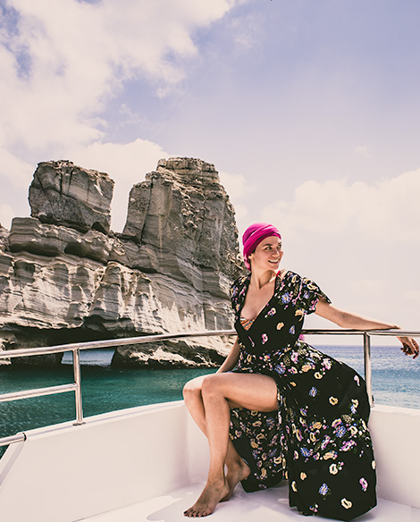 A woman (me) sits on a boat and soft rocks of Kleftikos can be seen behind her.
