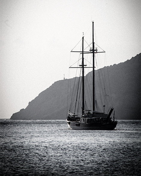 A black and white image of a ship sailing away in Sifnos, Greece.