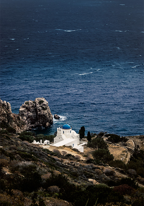 A tiny white church on a cliff.  Below it, blue waters and above it, more rock.  A small church in Sifnos, Greece - 7 day Greece Itinerary.