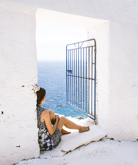 A woman (me) sits in a white doorway, blue water behind her.  The woman is facing the water - away from the camera.