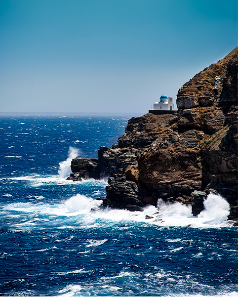 A tiny church stands on a tall cliff, and beneath it waves are hitting the rock.