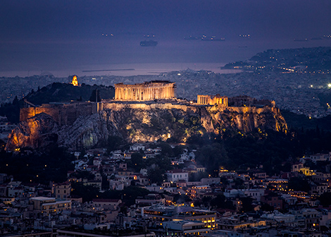 The view of the Acropolis at night. Taken from a distance, the acropolis is lit up. In the background and foreground buildings and in the far foreground the sea with ships. 7 days off the beaten path in Greece - Acropolis