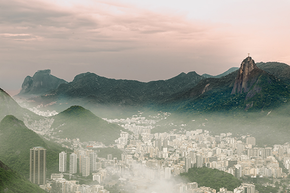 The city of Rio shot from far above.  In the valley white buildings appear and they are surrounded by mountains with blooming trees.  In the foreground, rises the statue of Christ the redeemer.  Lightweight carry on luggage - travel tips.