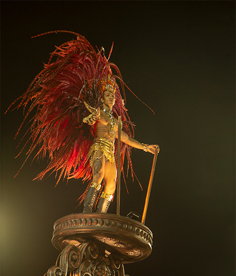 Rio Carnival - the complete beginners guide.  A male performer in the Rio Carnival standing on a float and wearing a large red head dress.