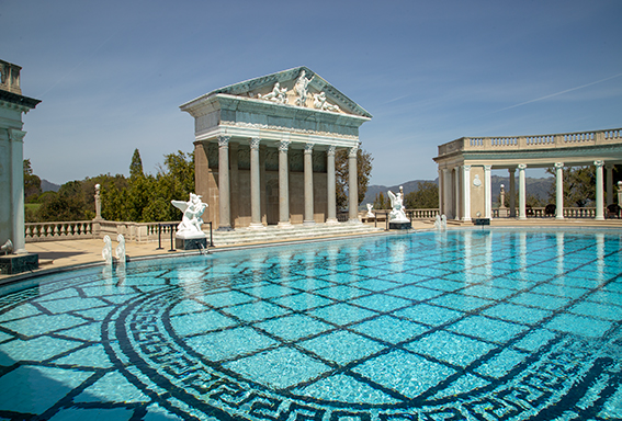 the outdoor pool at hurst castle, featuring a large pool with water, greek inspired details and a pool house with green columns.