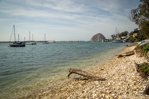 Morro Bay, California - Pacific Coast Highway.  A large boulder in the background, ocean and small boats in the foreground.