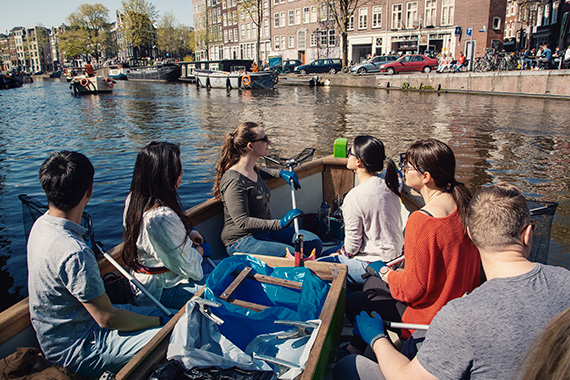 6 people on a boat in an amsterdam canal. each person has a net and is wearing gloves to help fish out the garbage from the canal - things to do in amsterdam - plastic whale.
