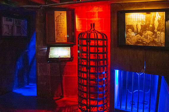 an exhibit at the museum of torture featuring a large metal cage, paintings.  set up in a small, medieval like room.