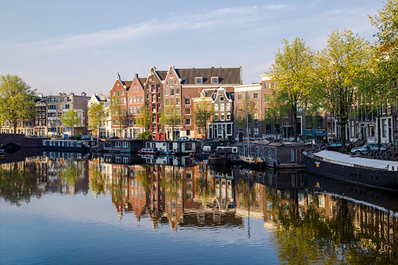 things to do in amsterdam - row houses and a canal with boats in the morning.