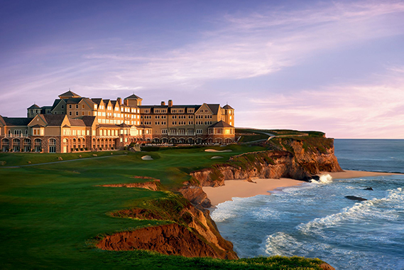 the ritz carlton in half moon bay - a hotel that sits on a shore, cliffs and water in the background.