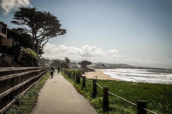 paved pathway in half moon bay, with homes on one side and the beach on the other side.  pch stop.