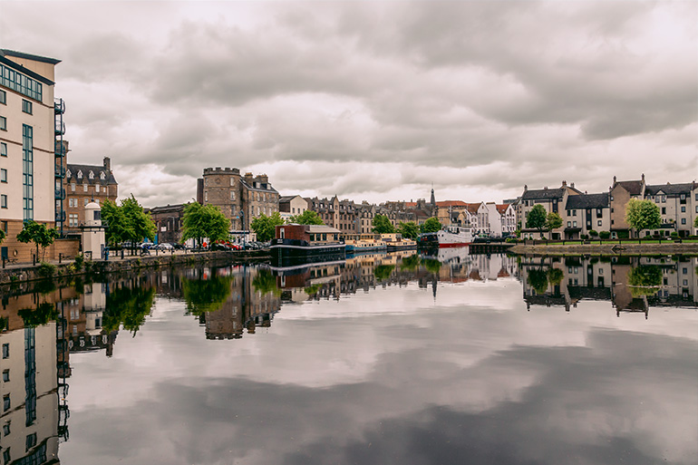 Leith neighborhood in Edinburgh.  attractive buildings reflected in still waters, overcast sky and leafy trees in the background.
