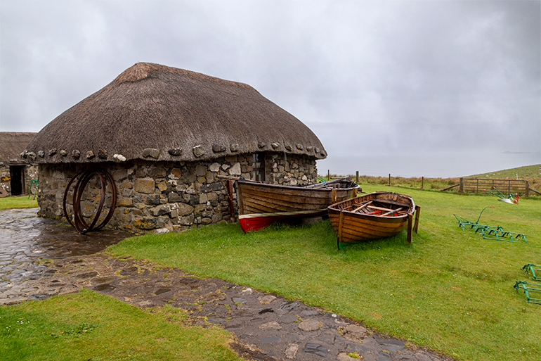 A small stone shack with a thatched roof, two small wooden boats out front.  Traditional tools on the lawn in front of the boats.