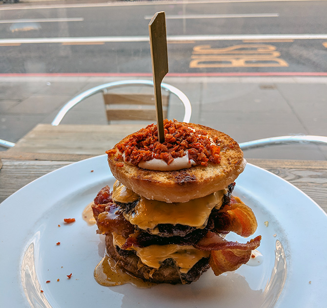 A donut burger - two meat patties, bacon, cheese between two slices of a donut.
