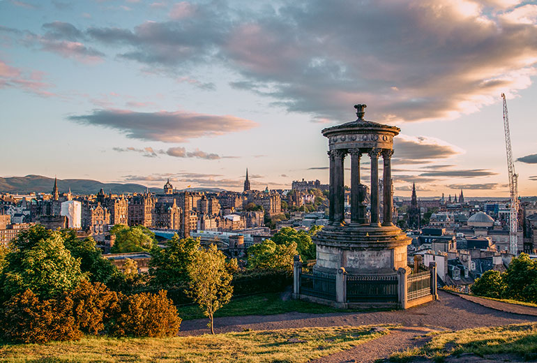 A 19th century column monument set against the backdrop of Edinburgh skyline, a crane and buildings in the background, a cloudy sky.