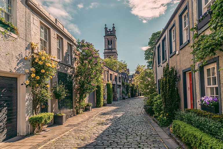 A cobblestone street lined with blooming flowers and old buildings.  A small tower appears in the background.