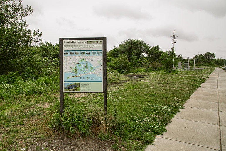 """A sign that says """"Jamaica Bay Greenway.""""  A map under the sign, grass and trees around it and a road on the right side of the sign.  The entry to dead horse bay."""