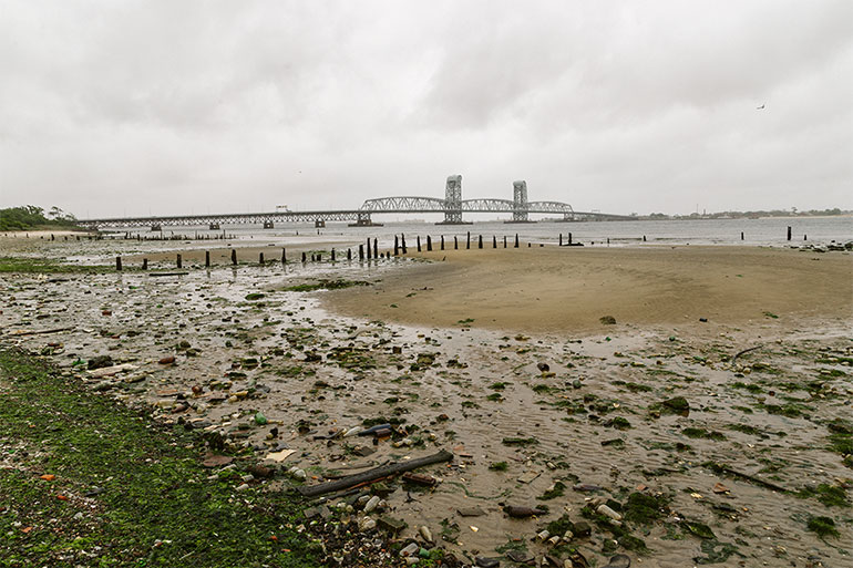 A littered beach and a bridge in the background, cloudy skies overhead.