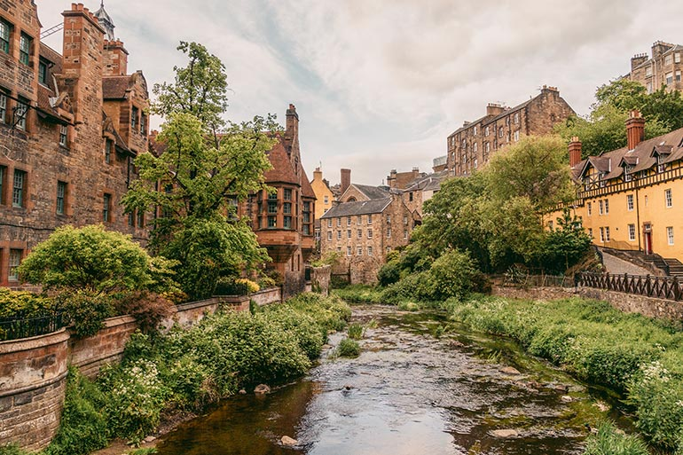 Dean Village in Edinburgh.  A stream of water, pretty old homes line both sides, leafy trees and greens.  A peaceful scene.