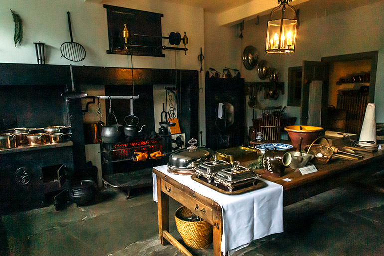 A kitchen in a Georgian period home.  A large wooden table set with period utensils, a fireplace with two teapots hanging over it.  Brass pots and pans.