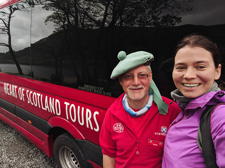 "A woman (me) in a rain jacket and a man (my guide) in traditional Scottish wear pose in front of a red van with the words ""heart of scotland tours.""  Reflections of the highlands in the windows of the van."