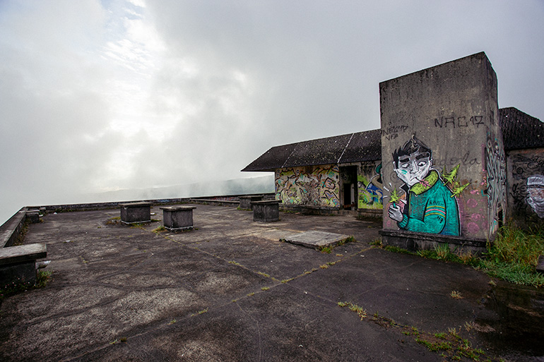 The rooftop of the abandoned hotel, with a graffiti portrait and grass sprouting from the floor.  Foggy morning, and the sun is covered by clouds.
