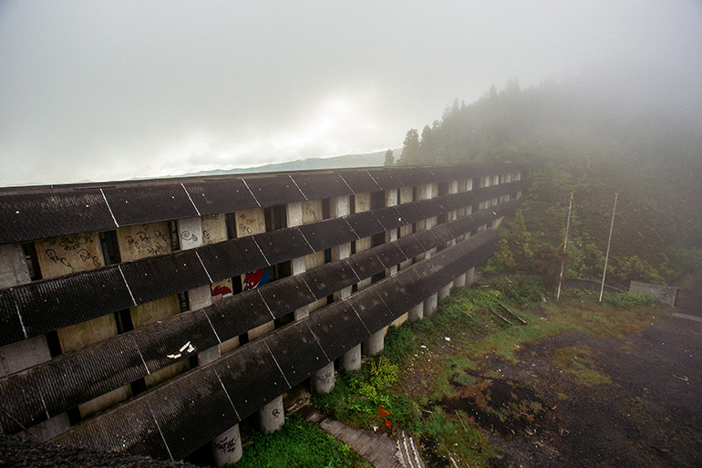 External view of the hotel, four floors and external corridors.  Trees and fog in the background.