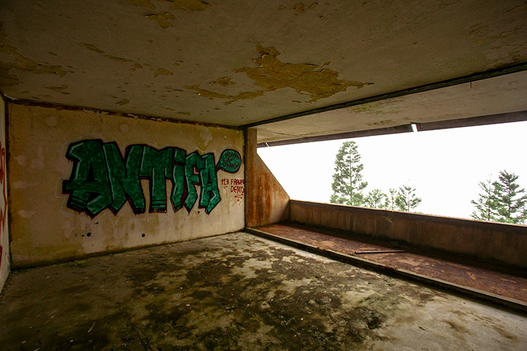 Inside of the ruined hotel graffiti with the words Antifa.  Through an opening in the wall, trees and fog in the background.