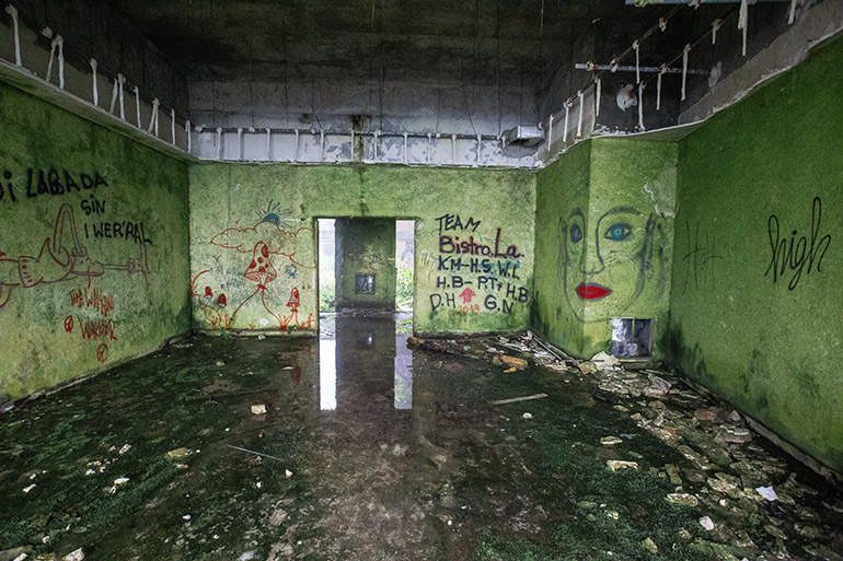 A large room with graffiti and floor littered with garbage - an abandoned suite in Monte Palace Hotel.  The graffiti includes a woman's face and words in Portugese.